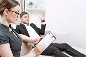pic of psychologist  - Young man wearing a black suit lying on a couch telling his problems and gesticulating - JPG