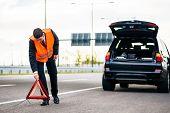 image of breakdown  - Man with car breakdown erecting warning triangle on road - JPG