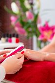 foto of beauty parlor  - Woman choosing nail polish in beauty parlor to receive a manicure - JPG
