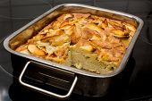 stock photo of oven  - Apple cake with one piece cut in the rectangular steel oven - JPG