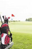 stock photo of golf bag  - Golf club bag at golf course against clear sky - JPG