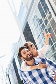 foto of piggyback ride  - Happy woman showing something to man while enjoying piggyback ride in city - JPG