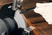 image of friction  - Knife sharpener and hand with blade on wooden table - JPG
