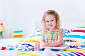 pic of little young child children girl toddler  - Toddler girl reading a book in bed - JPG