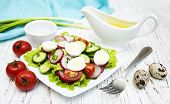 stock photo of radish  - Spring salad with tomato cucumbers and radish on a wooden background - JPG