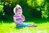 stock photo of little young child children girl toddler  - Child eating ice cream. Kids play outdoors enjoying sweet snack on a hot summer day. Children eat icecream. Toddler kid playing in the garden. Little girl with vanilla and chocolate ice cone. ** Note: Soft Focus at 100%, best at smaller sizes - JPG