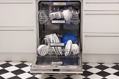 stock photo of dishwasher  - Dishwasher loades in a kitchen with clean dishes and blue light - JPG