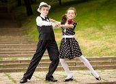 picture of waltzing  - Portrait of a very young couple in retro garment posing at the camera - JPG