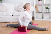image of do splits  - Stretched retired woman doing splits at yoga exercises - JPG