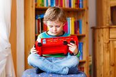 stock photo of daycare  - Little blond kid boy playing with wooden toy bus indoors - JPG