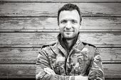 foto of camouflage  - Young smiling Caucasian man in camouflage outdoor black and white portrait over rural wooden wall - JPG