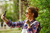 pic of lollipop  - Teen girl with a photo of herself with smartphone - JPG