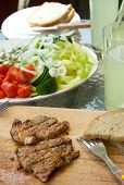 stock photo of pork chop  - Vertical photo of grilled pork steak cut on stripes on chopping board with fork and bread - JPG