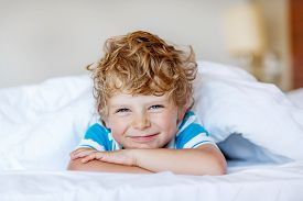 picture of boys night out  - Beautiful happy kid boy after sleeping in his white bed - JPG