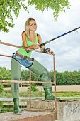 picture of fisherwomen  - smiling young blond woman fishing at pond - JPG