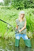 stock photo of fisherwomen  - smiling young blond woman fishing in pond - JPG