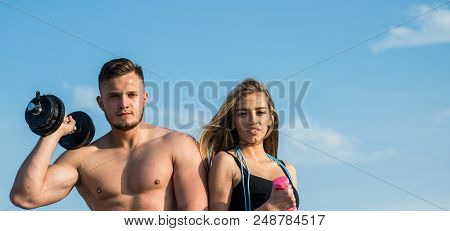 poster of Fitness. Fitness Training On Blue Sky. Fit Man And Woman With Fitness Tools Outdoor. Fitness Trainer