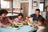 Family Enjoying Meal Around Table At Home Together poster
