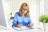 Portrait Of Mature Executive Businesswoman Doing Some Paperwork While Sitting At Her Workstation At  poster