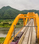 Top View Of Train Crossing Yellow Arch Bridge Over A River In Countryside Under Cloudy Overcast Sky. poster
