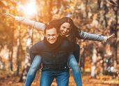 Young Happy Couple Have Fun In Park In Autumn. Happy Time Spending Outdoor Concept. Young Family Hav poster