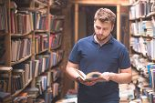 Student Portrait Of A Beard Standing In A Public Library Between Shelves And Looking At A Book In Hi poster