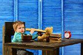 Child In Kindergarten. Little Child Eat French Baguette. Child Enjoy Tasty Dinner Sitting At Table.  poster
