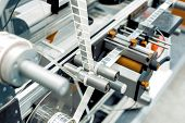 Automatic Labeling Machine. The Labeled Tape Is Located Between The Feed Rollers. poster
