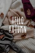 Background With Warm Sweaters And The Inscription Hello Autumn. Pile Of Knitted Clothes With Autumn  poster