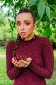 Beautiful Young Woman With Long Braid And Cherry Earrings Holding Cherry In Hands And One Cherry In  poster