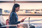 Airport phone travel Asian businesswoman using mobile smartphone in business class lounge waiting fo poster