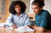 High School Tutor Giving Male Student One To One Tuition At Desk poster