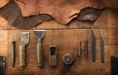 Leather craft or leather working. Leather working tools and cut out pieces of brown leather on craft poster