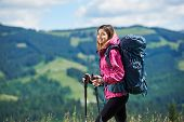 Close-up Portrait Of Smiling Active Female Backpacker With Backpack And Trekking Poles, Wearing Spor poster