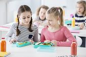 Two Young Girls During Snack Time In A School Looking Into Each Others Lunch Boxes With Healthy Veg poster