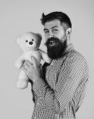 Man Holds Teddy Bear On Blue Background. Tenderness And Childish Mood Concept. Guy With Happy Face P poster
