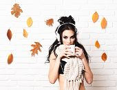 Girl With Serious Face Holds And Drinks Cup Of Coffee On White Brick Wall Background. Autumn Club Pa poster