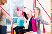 Senior people at fitness course in gym exercising with stretch band poster