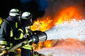 Firefighter - Firemen extinguishing a large blaze, they are standing with protective wear in front o poster