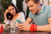 Wrist Band. Handsome Blonde-haired Modern Man Wearing Red Floral Wrist Band Using His Smart Phone poster