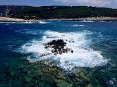 Aerial above waves crashing over rugged rocky coastline poster