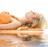 stock photo of beautiful lady  - beautiful lady with orange towels in spa salon - JPG