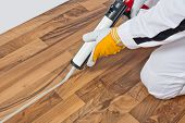 stock photo of penetration  - Worker Applies Silicone Sealant Spaces Of Old Wooden Floor to prevent movements - JPG