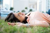 Woman daydreaming lying on grass at the park