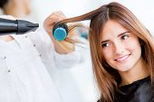 stock photo of hair blowing  - Woman portrait blow drying her hair at the beauty salon - JPG