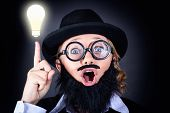 stock photo of stereotype  - Crazy male scientist wearing nerd glasses fake moe and plastic beard pointing up to bright lightbulb with expression of genius - JPG