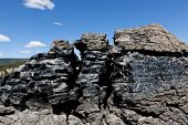foto of obsidian  - A large formation of black obsidian lava flow cracked by weather and erosion in Newberry National Volcanic Monument Oregon - JPG