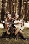 Hippie girls with guitar in a forest