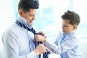 stock photo of youngster  - Photo of little boy helping his father tie necktie - JPG
