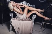 stock photo of silver-hair  - sexy beautiful girl with blond hair sitting on chair - JPG